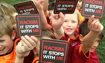 Kids holding signs up stating: Racism. It stops with me