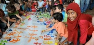 Children painting colourful stick figures on large canvas