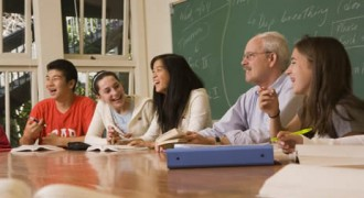 Laughing students and teacher sitting at table