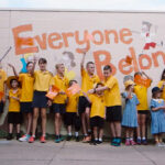 School children waving harmony day flags in front of wall with writing: Everyone belongs