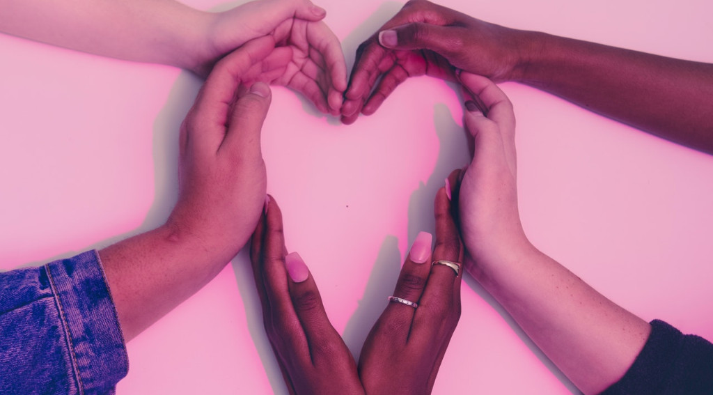 Hands from diverse cultural backgrounds making a heart shape