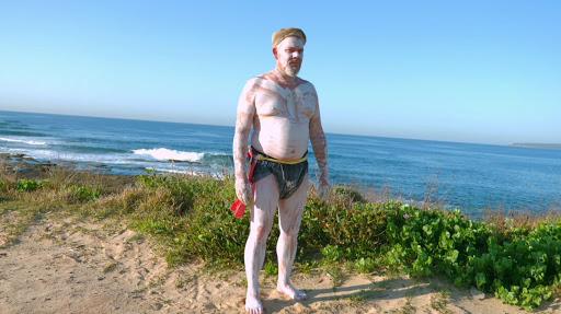 Indigenous man standing by ocean
