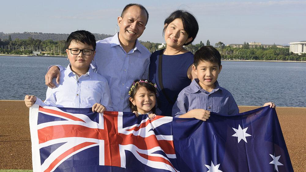 Family holding Australian flag on Citizenship Day
