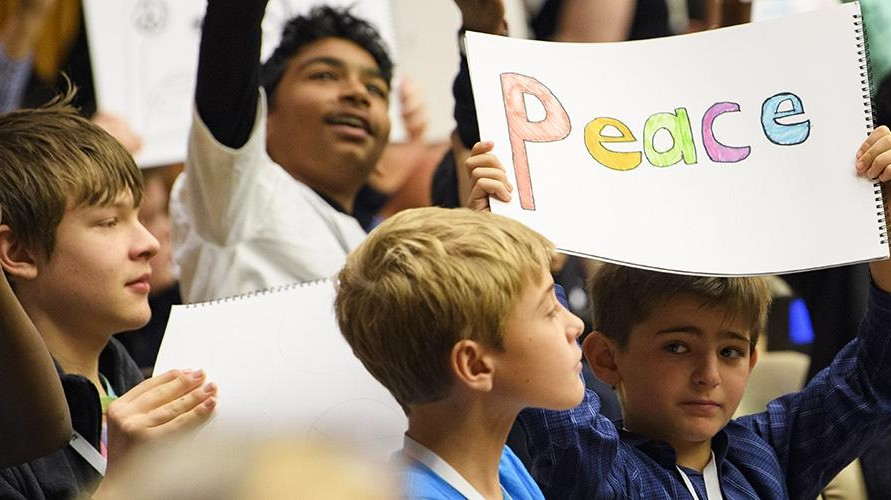Boy in crowd holding 'Peace' sign