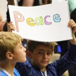 Boy holding peace sign in crowd